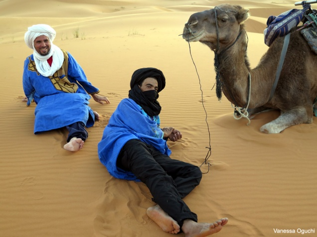 Berber guides relaxing by camel in the Sahara Desert